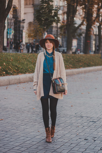 How to wear: beige knit open cardigan, navy denim shirt, navy skater skirt, brown leather lace-up flat boots