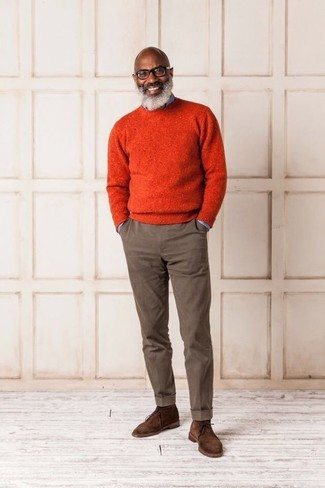 How to wear: orange crew-neck sweater, light blue denim shirt, brown chinos, brown suede desert boots