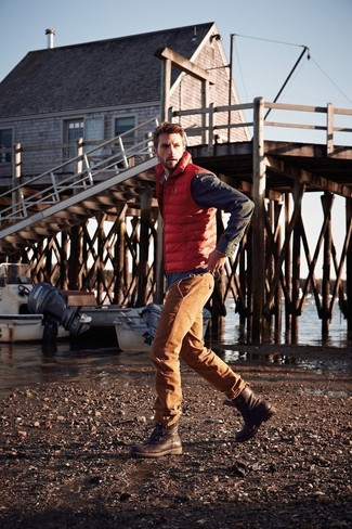 How to wear: orange gilet, charcoal long sleeve shirt, orange jeans, dark brown leather work boots