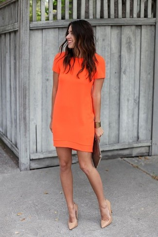 Rock an orange shift dress to feel confidently and look fashionably. This outfit is complemented perfectly with khaki leather pumps.