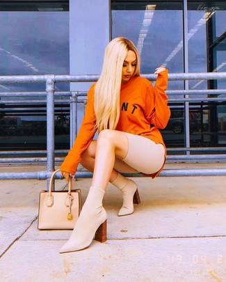 How to wear: orange print sweatshirt, beige bike shorts, beige elastic ankle boots, beige leather tote bag