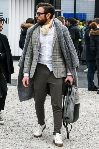 How to Wear a Grey Overcoat In Winter: A grey overcoat and charcoal chinos paired together are the perfect combo for men who appreciate polished looks. To bring a more casual feel to this look, complete your ensemble with white leather low top sneakers. When staying inside on a cold winter day is not a possibility, this ensemble just might get you through the day.