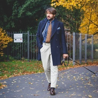 1200+ Cold Weather Outfits For Men: Pairing a navy overcoat and white dress pants will prove your sartorial expertise. To add a touch of stylish effortlessness to this outfit, introduce dark brown leather tassel loafers to the mix.