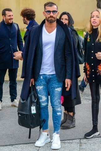 How to Wear Blue Ripped Skinny Jeans For Men: To put together a casual getup with a clear fashion twist, pair a navy overcoat with blue ripped skinny jeans. Introduce white leather low top sneakers to the mix and the whole ensemble will come together.