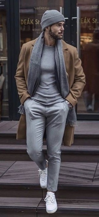 How to wear: camel overcoat, grey crew-neck sweater, grey chinos, white canvas low top sneakers