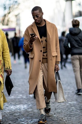 How to wear: camel overcoat, black print crew-neck sweater, khaki chinos, black athletic shoes