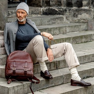How to Wear a Burgundy Leather Backpack For Men: This off-duty combination of a grey overcoat and a burgundy leather backpack comes in handy when you need to look stylish but have zero time. A pair of dark brown leather loafers effortlesslly dresses up any ensemble.