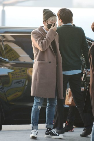 How to Wear a Camel Overcoat: A camel overcoat and blue ripped jeans are the kind of a no-brainer casual combination that you need when you have zero time. A pair of black and white canvas low top sneakers will be a stylish addition for your ensemble.