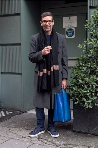 500+ Outfits For Men After 50: A charcoal overcoat and navy chinos are absolute essentials if you're planning a smart casual wardrobe that holds to the highest fashion standards. Let your sartorial expertise really shine by finishing your getup with a pair of navy canvas low top sneakers. Wondering how to dress as you go into your 50s? This combination is the perfect answer.
