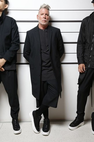 How to wear: black overcoat, black henley shirt, black shorts, black and white leather low top sneakers