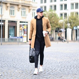How to wear: camel overcoat, black hoodie, black ripped skinny jeans, white athletic shoes