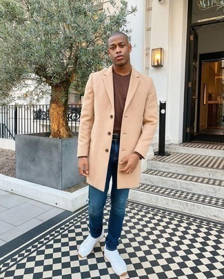 Blue Jeans Outfits For Men: If the dress code calls for a casually neat ensemble, consider teaming a camel overcoat with blue jeans. Let your sartorial savvy truly shine by completing your look with white athletic shoes.