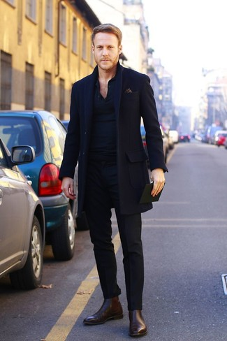 Pairing a black overcoat and black dress pants will create a powerful and confident silhouette. Dark brown leather chelsea boots will contrast beautifully against the rest of the look.