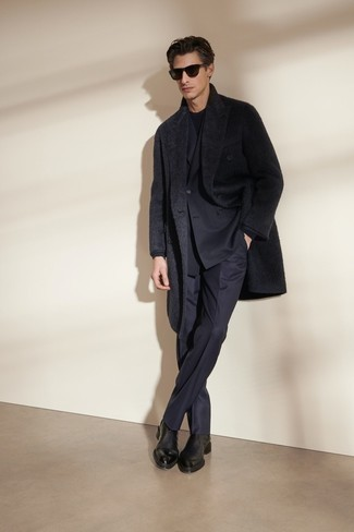 Black Overcoat Outfits: A black overcoat and a navy suit are certainly worth being on your list of veritable menswear staples. Introduce black leather chelsea boots to your ensemble to inject a sense of stylish casualness into this outfit.