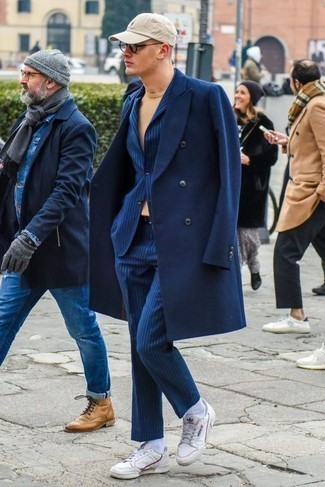 How to Wear a Navy Overcoat: Make a head-turning statement anywhere you go in a navy overcoat and a blue vertical striped suit. White leather low top sneakers will give a dressed-down touch to this look.