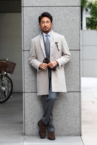 How to wear: grey overcoat, grey vertical striped suit, light blue dress shirt, dark brown suede desert boots