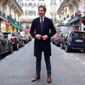 How To Wear a Black Suit With Brown Shoes: Channel your inner James Bond and consider pairing a black suit with a black overcoat. Brown leather oxford shoes pull the ensemble together.
