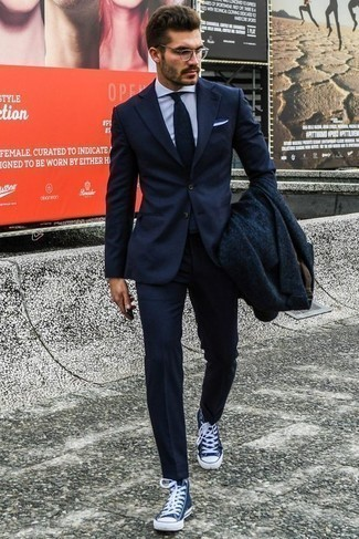 How to Wear a Navy Overcoat: A navy overcoat and a navy suit make for the ultimate smart look. For something more on the cool and laid-back side to complete this look, add navy and white canvas high top sneakers to the equation.