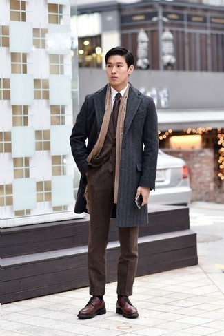 Fashion for 20 Year Old Men: What To Wear In a Dressy Way: This elegant combination of a charcoal overcoat and a dark brown suit is a favored choice among the sartorially superior men. You know how to tone it down: brown leather brogues. This outfit illustrates that dressing your age and looking stylish are not mutually exclusive things for a 20-year-old gent.