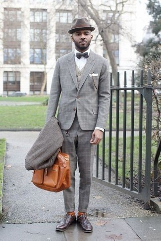 How to Wear a Grey Overcoat: Teaming a grey overcoat and a grey plaid suit is a fail-safe way to inject refinement into your wardrobe. Add a pair of dark brown leather oxford shoes to the mix to pull the whole thing together.