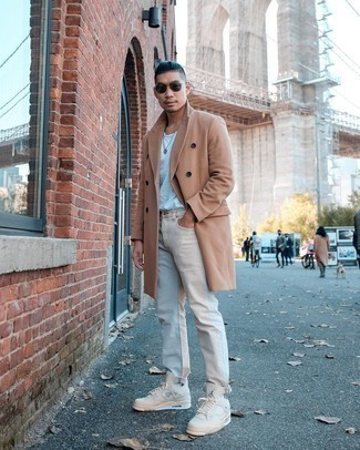 Beige Jeans Outfits For Men: A camel overcoat and beige jeans are the kind of a foolproof getup that you so desperately need when you have no time to dress up. Dial down this outfit by wearing beige canvas low top sneakers.
