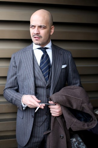 How to wear: dark brown overcoat, grey vertical striped three piece suit, white dress shirt, navy vertical striped tie