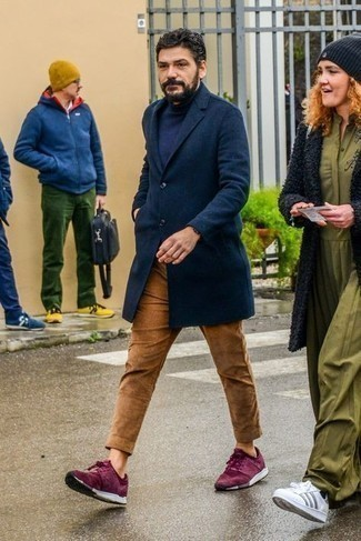 Black Watch Chill Weather Outfits For Men: A navy overcoat and a black watch are a laid-back combination that every modern gentleman should have in his wardrobe. Purple athletic shoes are an easy way to inject a touch of stylish casualness into this ensemble.