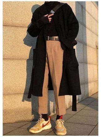 Men's Outfits 2021: This pairing of a black overcoat and khaki chinos makes for the perfect base for an outfit. Complement your getup with tan athletic shoes to bring a dose of stylish nonchalance to your getup.