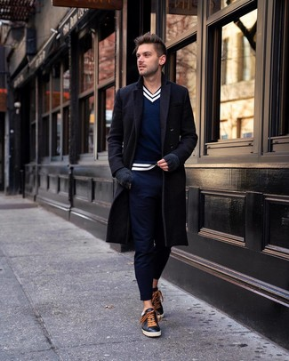 How to wear: black overcoat, navy and white v-neck sweater, navy chinos, black leather low top sneakers