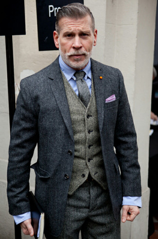 Nick Wooster wearing Charcoal Overcoat, Grey Herringbone Wool Waistcoat, Light Blue Dress Shirt, Charcoal Herringbone Wool Dress Pants