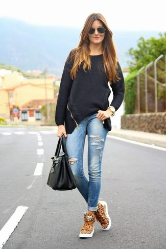 Team a black oversized sweater with blue ripped slim jeans for a trendy and easy going look. Tan leopard high top sneakers will add some edge to an otherwise classic look.