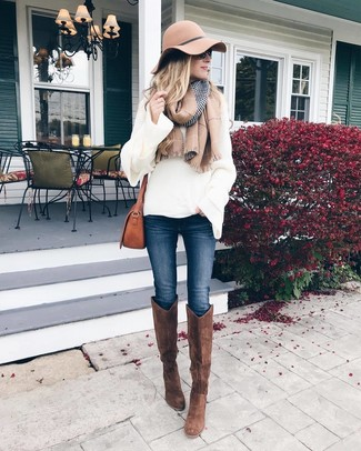 Brown Suede Knee High Boots Outfits: If the setting permits off-duty style, you can rely on a white knit oversized sweater and navy skinny jeans. Brown suede knee high boots are the most effective way to add an element of polish to this ensemble.
