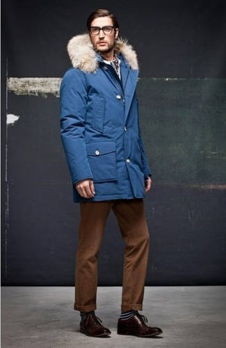 Cómo combinar: parka azul, pantalón chino en tabaco, zapatos oxford de cuero en marrón oscuro, calcetines de rayas horizontales negros
