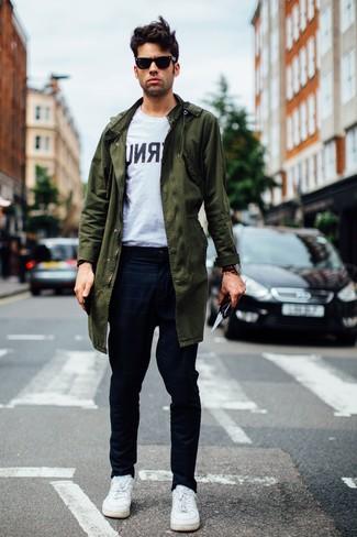 Cómo combinar: parka verde oliva, camiseta con cuello circular estampada en blanco y negro, pantalón chino a cuadros azul marino, tenis de cuero blancos