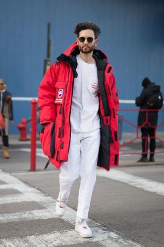 Cómo combinar: parka roja, camiseta con cuello circular estampada en blanco y rojo, pantalón chino blanco, tenis de cuero blancos
