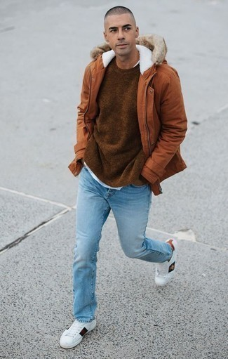 How to Wear White Print Leather Low Top Sneakers For Men: This combo of a tobacco parka and light blue jeans looks put together and instantly makes you look on-trend. Introduce a pair of white print leather low top sneakers to the mix and ta-da: the outfit is complete.