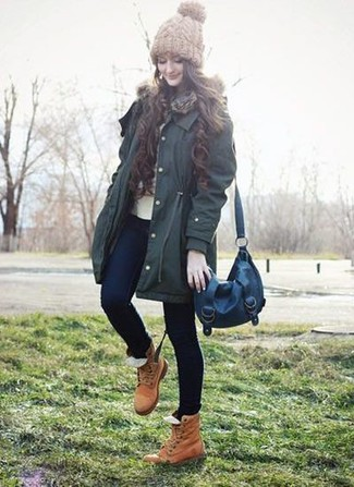 How to wear: dark green parka, beige crew-neck sweater, navy skinny jeans, tan leather lace-up flat boots