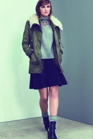 Cómo combinar: parka verde oliva, jersey de cuello alto de punto gris, falda skater negra, botines de cuero con recorte negros