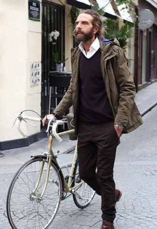 Cómo combinar: parka verde oliva, jersey de pico en marrón oscuro, camisa de vestir blanca, pantalón chino en marrón oscuro