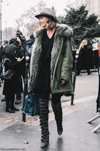 Cómo combinar: parka verde oliva, jersey de pico negro, falda skater negra, botas sobre la rodilla de cuero negras