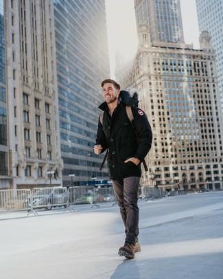 Cómo combinar: parka negra, vaqueros en gris oscuro, botas casual de cuero marrónes, mochila de cuero marrón claro