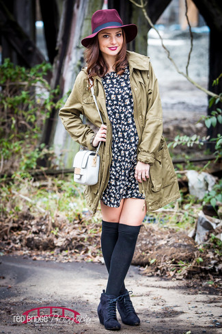 Let everyone know that you know a thing or two about style in an olive parka and a black floral skater dress. Elevate this ensemble with black suede lace-up ankle boots.