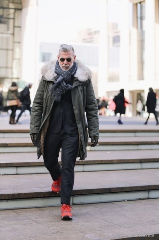 Wear a parka with a black suit for a dapper casual get-up. For footwear go down the casual route with red trainers.