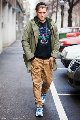 How to wear: olive parka, black print sweatshirt, khaki chinos, white athletic shoes