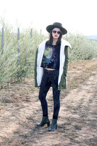 Cómo combinar: parka verde oliva, top corto estampado negro, vaqueros pitillo de camuflaje azul marino, botines de cuero verde oscuro