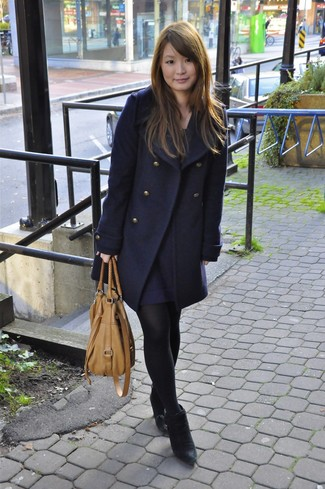 Consider pairing a navy peacoat with a navy swing dress to bring out the stylish in you. This outfit is complemented perfectly with black suede ankle boots.