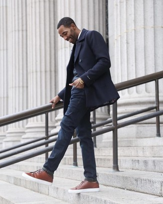 How to Wear a Grey V-neck Sweater For Men: Parade your credentials in menswear styling by wearing this off-duty combination of a grey v-neck sweater and navy jeans. As for shoes, introduce a pair of brown leather low top sneakers to this ensemble.