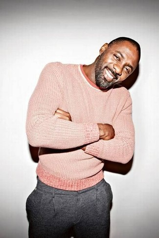 Pair a pink crew-neck sweater with grey wool trousers for a sharp, fashionable look.