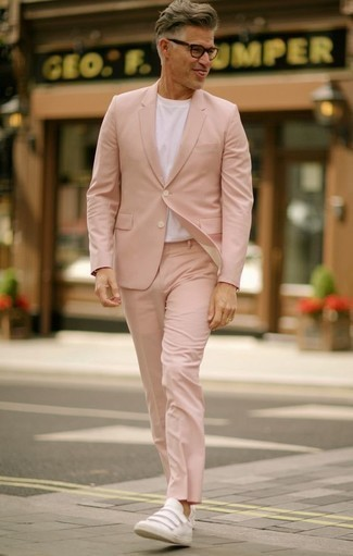 How to Wear a Pink Suit: You'll be amazed at how easy it is for any gent to throw together this effortlessly classic outfit. Just a pink suit combined with a white crew-neck t-shirt. A pair of white leather low top sneakers easily kicks up the fashion factor of this getup.
