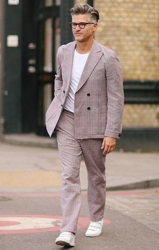 How to Wear a Pink Suit: A pink suit and a white crew-neck t-shirt are the kind of a fail-safe getup that you so desperately need when you have zero time. White leather low top sneakers are an easy way to give a sense of stylish nonchalance to your look.
